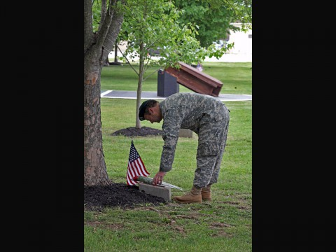 A Soldier from the 5th Special Forces Group (Airborne) places a rose on the marker of an oak tree on Gabriel Field during the Gold Star ceremony May 17, 2014, at Fort Campbell, Ky. Soldiers, Families, and friends, both past and present, gathered together to remember, reflect, and celebrate the lives of those that paid the ultimate sacrifice. (Sgt. Seth Plagenza)