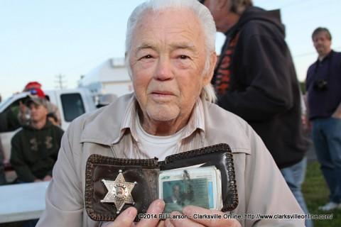 Charles Hinton holding up his Sheriff Deputy Badge.