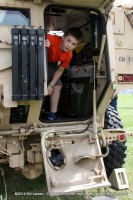 A boy peeks out the back of an APC