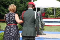 A ROTC cadet escorts a family member after placing a rose at the Montgomery County War Memorial