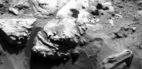 """This May 5, 2014, image from the Navigation Camera on NASA's Curiosity Mars rover shows two holes at top center drilled into a sandstone target called """"Windjana."""" The farther hole was created by the rover's drill while it collected rock-powder sample material from the interior of the rock."""