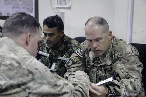 U.S. Army Lt. Col. Travis Thompson (right), the deputy commander of 2nd Brigade Combat Team, 101st Airborne Division, listens to a peer while advising his counterpart with the 201st corps Afghan National Army at Forward Operating Base Gamberi in Laghman province, June 14, 2014. (Sgt. David Cox, 2nd Brigade Combat Team Public Affairs)
