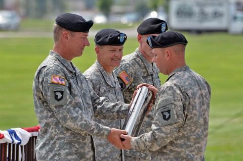 Maj. Gen. James C. McConville (left), outgoing commanding general, 101st Airborne Division (Air Assault), is presented with a ceremonial artillery shell casing as a memento as Gen. Daniel B. Allyn (center), commanding general, U.S. Army Forces Command, looks on during a change of command ceremony, June 20, 2014, at Fort Campbell, Ky. (U.S. Army photo by Larry Noller)