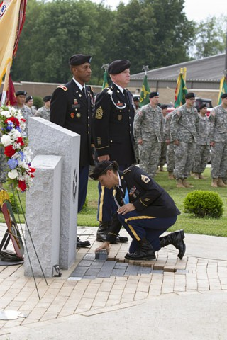 "Staff Sgt. Cybelle Rey, a human resources noncommissioned officer with the 101st Special Troops Battalion, 101st Sustainment Brigade ""Lifeliners,"" 101st Airborne Division (Air Assault), places an engraved brick in memory of a fallen Soldiers at the Memorial Monument during a Memorial Brick Laying Ceremony, June 9, 2014, at Fort Campbell, KY. (U.S. Army photo by Sgt. 1st Class Mary Rose Mittlesteadt, 101st Sustainment Brigade Public Affairs)"