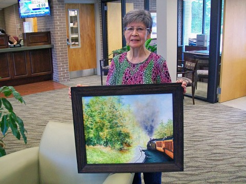 Kay Limirande holding one of her paintings in Planters Bank.