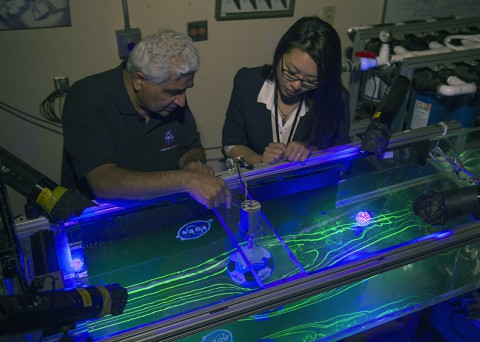 Dr. Rabi Mehta and Christina Ngo view a test of a of a traditional 32-panel football scale-model in the 17-inch water channel. Flow patterns are visualized using florescent dye and black lights. (NASA's Ames Research Center)