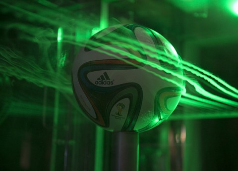 A close up of the Brazuca ball in Ames' Fluid Mechanics Laboratory's two-foot by two-foot wind tunnel. Smoke highlighted by lasers visualizes air flow around the ball. (NASA's Ames Research Center)