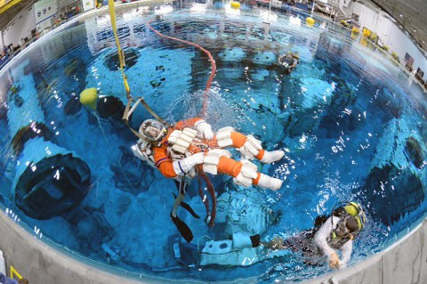 Steve Bowen is lowered into the Neutral Buoyancy Laboratory at Johnson Space Center to test spacewalk suits and tools for a mission to an asteroid. (NASA)