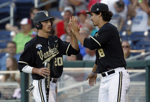 Vanderbilt Commodores runner Bryan Reynolds (20) celebrates his run with pitcher Jared Miller (28) against the Texas Longhorns during game thirteen of the 2014 College World Series at TD Ameritrade Park Omaha. (Bruce Thorson-USA TODAY Sports)