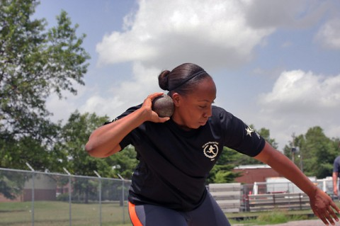 Sgt. Kadina Baldwin heaves a heavy shot put ball July 1, 2014 at Fort Campbell's Fryar Stadium, demonstrating the winning technique she used during the Army Warrior Games trials June 15-20 at the U.S. Military Academy, West Point, New York. Baldwin took the bronze medal in shot put and gold medals in wheelchair basketball and sitting volleyball. (U.S. Army photo by Stacy Rzepka)