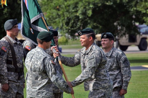 Col. John W. Brennan, commander of the 5th Special Forces Group (Airborne), passes the colors to Lt. Col. Brent W. Lindeman, the incoming commander of 3rd Battalion, 5th SFG(A), during a change of command ceremony, July 1, 2014, held at Gabriel Field. (Pfc. Robert Vanegas)
