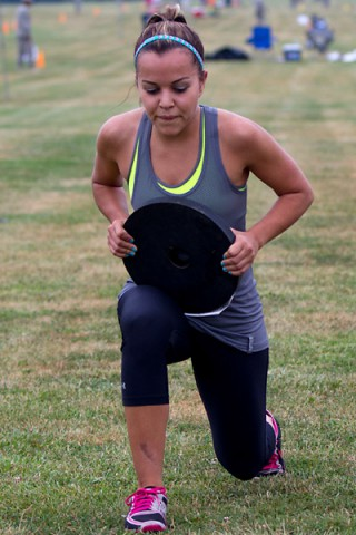 Autumn Gonzalez, a military spouse and employee at the Fort Campbell Child and Youth Services, lunges with 25 pounds across a 30 meter course as part of the 2014 Eagle Challenge Fitness Tour Functional Fitness Challenge July 19, at Fort Campbell. (Leejay Lockhart)