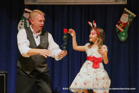 Magician Russ Nowack astounds a young girl with one of his magic tricks