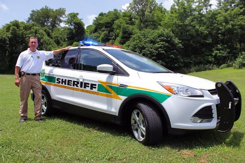 Sheriff John Fuson unveils the new fleet vehicle, a 2014 Ford Escape that costs less, has a higher mile per gallon rating and is more environmentally friendly.