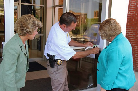 Bowers and McMillan assist Fuson in applying the sticker signifying green certification on the Public Safety Complex.