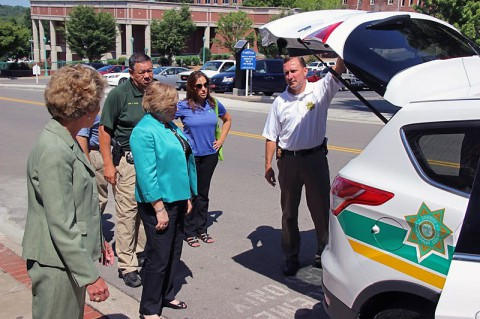 Fuson shows Mayors Carolyn Bowers and Kim McMillan the 2014 Ford Escape.