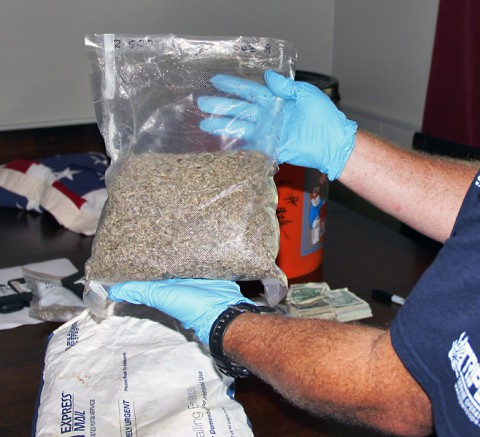 A Drug Task Force agent holds up a bag of synthetic marijuana found at the home of Robert Joseph Nolen.