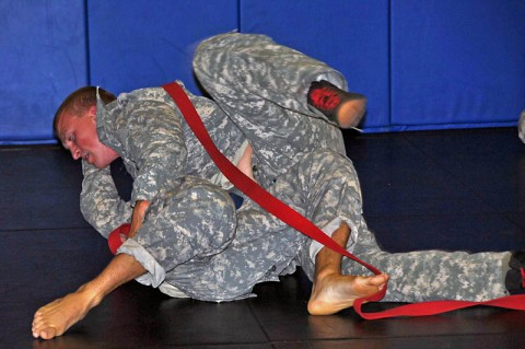 Sgt. Derek A. Youngs (right), a wheeled vehicle mechanic with 1st Platoon, Headquarters and Headquarters Company, 160th Special Operations Aviation Regiment (Airborne) transitions from side control to full mount during a combatives tournament June 25, 2014. (Sgt. 1st Class Thaddius S. Dawkins II)