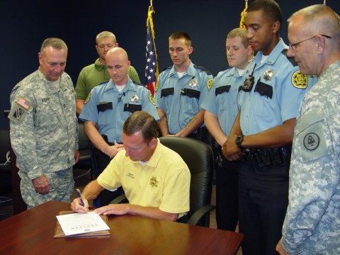 Sheriff John Fuson signs the Statement of Support which was also signed by Defense Secretary Chuck Hagel, while MG Robert Harris, CSM Dan Jennings and Deputies Michael Howard, Brandon Theis, James Owens, Marsel Gray, Theodore Rooding look on.
