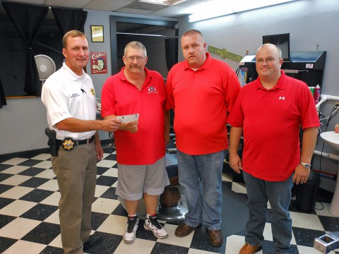"""Sheriff John Fuson is presented with a check from Uncle Joe's Barber Shop in honor of Deputy David """"Bubba"""" Johnson. Pictured are Fuson, Greg Cooper, Brad Young and Jonathon Uzzle."""
