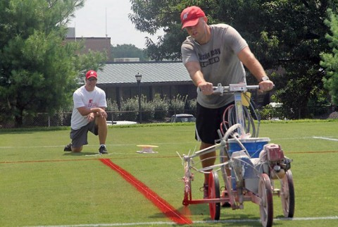 Assistant soccer coach Jeremy Sullivan lines off the soccer field with football yard lines with the help of football assistant Josh Richards. (APSU Sports Information)