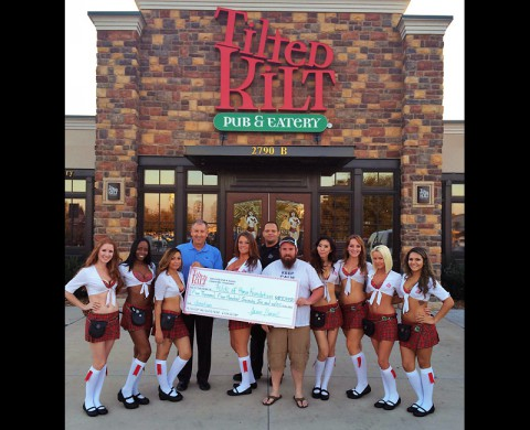 Folds of Honor Vice President of Corporate Relations Dave Dierinzo accepts a donation from the Tilted Kilt Assistant Manager Chris Williams, Nashville Chive Administrator Whit Noble and the Tilted Kilt Girls. (Laura Thornton)