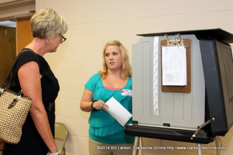 A poll worker explains the process to Melinda Shepard before she casts her ballot