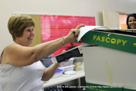 Joan Burke, a volunteer at the Teachers Warehouse grabs the first pack of the donated paper for Tonya Campbell, a sixth grade teacher at Richview Middle School.