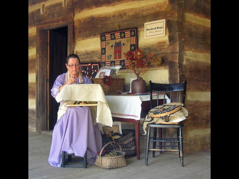 An interpreter seen here making an old-fashioned rug on the porch at LBL's The Homeplace. (Land Between the Lakes)