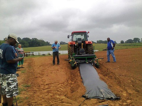 Billy & Teresa Reints McCraw demonstrating the plastic layer for plasticulture strawberries. This machine builds the beds in the soil, lays the plastic and the irrigation line all at the same time at McCraw's Strawberry Ranch.