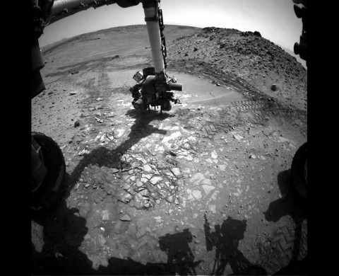 "This image from the front Hazcam on NASA's Curiosity Mars rover shows the rover's drill in place during a test of whether the rock beneath it, ""Bonanza King,"" would be an acceptable target for drilling to collect a sample. Subsequent analysis showed the rock budged during the Aug. 19, 2014, test. (NASA/JPL-Caltech)"