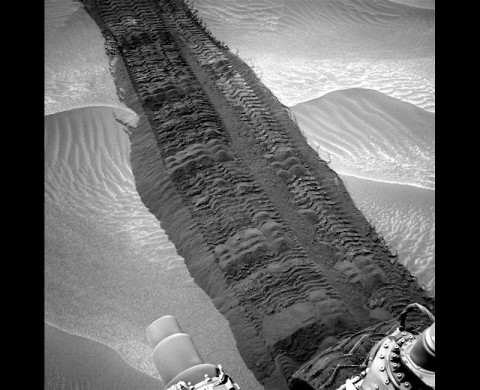 "This image from the Navigation Camera on NASA's Curiosity Mars rover shows wheel tracks printed by the rover as it drove on the sandy floor of a lowland called ""Hidden Valley"" on the route toward Mount Sharp. The image was taken on Aug. 4, 2014."