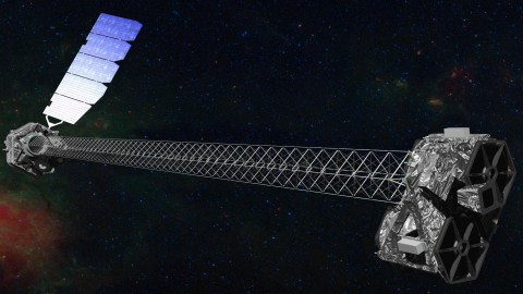 Artist's concept of NuSTAR on orbit. NuSTAR has a 10-m (30') mast that deploys after launch to separate the optics modules (right) from the detectors in the focal plane (left). The spacecraft, which controls NuSTAR's pointings, and the solar panels are with the focal plane. NuSTAR has two identical optics modules in order to increase sensitivity. The background is an image of the Galactic center obtained with the Chandra X-ray Observatory.