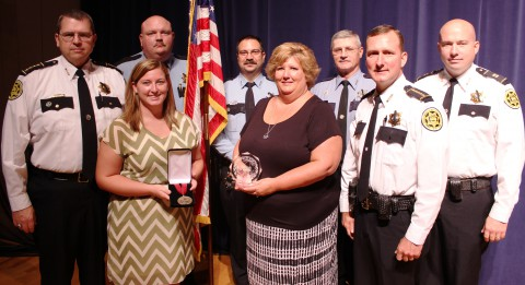 "From left, Chief John Smith, Shelby Johnson (daughter of Deputy David ""Bubba Johnson""), Sgt. Robert Boone, Deputy Daniel Brinkmeyer, Jennifer Johnson (wife of ""Bubba,"") Deputy Charles Hummel, Sheriff John Fuson and Captain Jesse Reynolds posing with the Three Stars of Tennessee Award, given to ""Bubba"" Johnson for giving his life to serve his community."