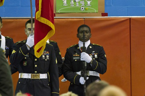"""Sgt. Matthew Webber (front), the NCO in charge of the honor guard, and Spc. Carlos R. Montenegro, another member of the 101st Special Troops Battalion """"Sustainers"""", 101st Sustainment Brigade """"Lifeliners"""", 101st Airborne Division (Air Assault), render respects during the playing of the national anthem during an assembly at the Marshall Elementary School Sept. 11 at Fort Campbell, KY. (U.S. Army photo by Sgt. Leejay Lockhart, 101st Sustainment Brigade)"""