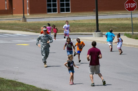 Pvt. Adam Grine, a native of Fostoria, Ohio, and a volunteer from Headquarters and Headquarters Detachment, 716th Military Police Battalion, 101st Sustainment Brigade, 101st Airborne Division, participates in a fun run with students during a back-to-school bash Saturday, at West Creek Elementary School in Clarksville, Tenn. Soldiers have volunteered at the school since it opened seven years ago. (Sgt. Leejay Lockhart, 101st Sustainment Brigade Public Affairs)