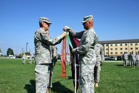 Col. George N. Appenzeller and Command Sgt. Major James Smith attach the Army Superior Unit Award ribbon on the Fort Campbell Warrior Transition Battalion colors Friday, Sept. 5, 2014. The Battalion earned this award for their actions in support of the combat operations in Afghanistan from October 1, 2014 through September 30, 2012