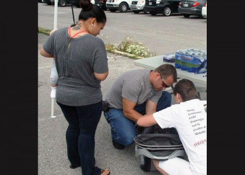 Montgomery County Sheriff's Deputy Jason Pike helps check a child seat.