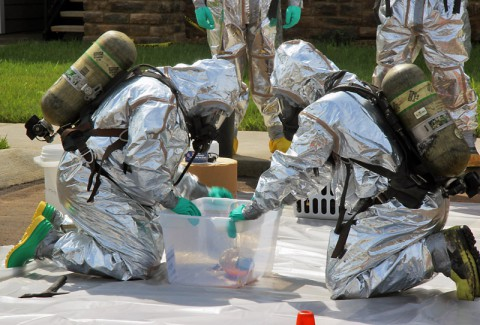 Agents with the 19th Judicial District Drug Task Force get ready to enter a meth lab in a Madison Street hotel with the help of Clarksville Fire Rescue and Montgomery County EMS.