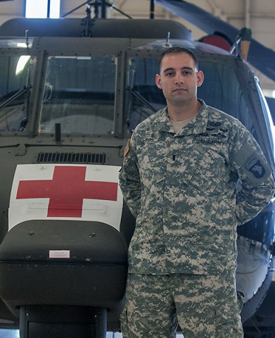 First Lt. Kenneth Danos, aeromedical-evacuation pilot, Company C, 6th Battalion, 101st Combat Aviation Brigade, 101st Airborne Division (Air Assault), poses in front of an HH-60M medevac Black Hawk Helicopter, here, Oct. 15, 2014. Danos was the honor graduate for receiving zero no-gos during his testing phase at the 2014 expert field medical badge lanes. (Sgt. Duncan Brennan, 101st CAB Public Affairs)