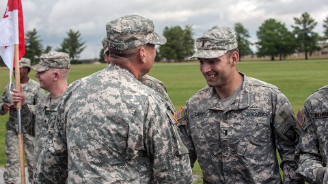 First Lt. Kenneth Danos, aeromedical-evacuation pilot, Company C, 6th Battalion, 101st Combat Aviation Brigade, 101st Airborne Division (Air Assault), is congratulated by Command Sgt. Maj. Stuart C. O'Black, command sergeant major, 101st CAB, after receiving his expert field medical badge, here, Oct. 3, 2014. Danos was the honor graduate, receiving zero no-gos during his testing phase. (Sgt. Duncan Brennan, 101st CAB Public Affairs)