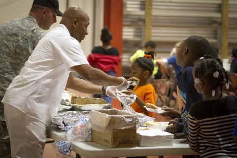 U.S. Army Sgt. 1st Class Christopher Roberts, food service sergeant with 3rd Battalion, 5th Special Forces Group (Airborne), serves food to children at the Boys and Girls Club of America in Christian County, Ky., Oct. 21, 2014, where he volunteers. (Sgt. Justin A. Moeller/U.S. Army)