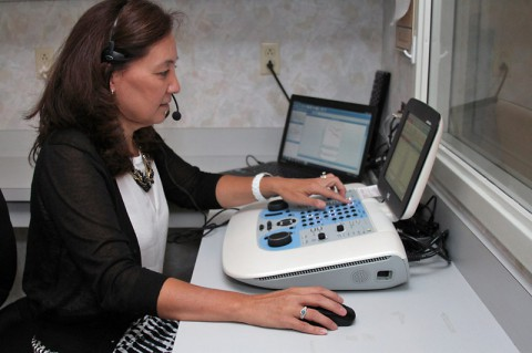 Dr. LeJeune of the Center for Audiology administering a hearing test.