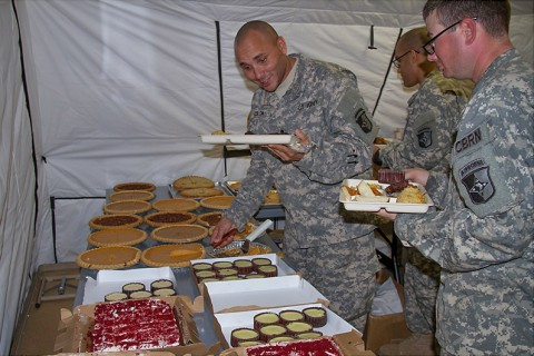 Soldiers with Task Force Lifeliner, Joint Forces Command – United Assistance dive into one of the many pies and desserts offered in the dining facility at brigade support area in Buchanan, Liberia, Nov. 27, 2014. (Sgt. 1st Class Mary Mittlesteadt, 101st Sustainment Brigade Public Affairs)