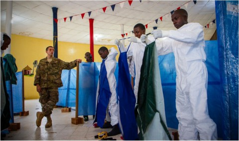 Senior Airman Joshua Douglass, an aerospace medical technician, watches as health care workers properly put on their personal protective equipment in Buchanan City, Nov. 21, 2014. Douglass is a part of the mobile training team that travels throughout Liberia to remote areas to train health care workers about Ebola and how to work in an Ebola treatment unit. Operation United Assistance is a Department of Defense operation in Liberia to provide logistics, training and engineering support to U.S. Agency for International Development-led efforts to contain the Ebola virus outbreak in western Africa. (Staff Sgt. Terrance D. Rhodes/U.S. Army)