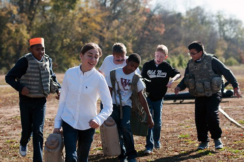 Students from West Creek Middle School in Clarksville, Tenn., carry water cans as part of an obstacle course set up by the 551st Military Police Company, 716th Military Police Battalion, 16th Military Police Brigade, supported by the 101st Sustainment Brigade, 101st Airborne Division, for a Veterans Day event Nov. 7 at West Creek Middle School. (U.S. Army photo by Sgt. Leejay Lockhart)