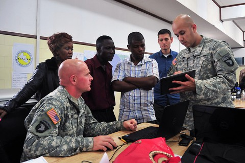 Chief Warrant Officer 2 Angel Mitre, right, the Joint Forces Command – United Assistance liaison officer to the National Ebola Crisis Center, Monrovia, explains to personnel from the Liberian Institute of Statistics – Geo-Information Services how an exchange of geospatial data between the JFC-UA and LISGIS created a more robust, useful product for organizations supporting Operation United Assistance, Oct. 29, 2014. (Sgt. 1st Class Nathan Hoskins)