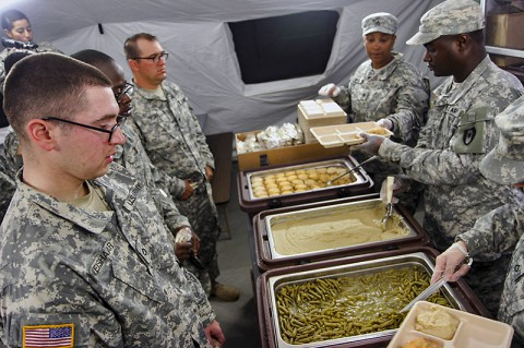 Soldiers wait in line for the first hot meal served on Barclay Training Center Nov. 9, 2014. Since arriving more than three weeks ago, service members have only consumed Meals, Ready-to-Eat. The hot meal gave service members something different to look forward to and boosted morale throughout the camp.  (Staff Sgt. Terrance D. Rhodes)