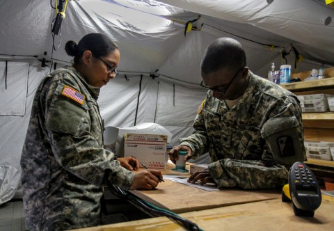 Spc. Brandon Carr, right, native of Kinston, North Carolina, and postal specialist for the 18th Human Resources Company, 82nd Special Troops Battalion, 82nd Sustainment Brigade, gives his 'stamp of approval' on a package that Spc. Savannah Martinez, left, native of Corpus Christi, Texas, and ammunition specialist for the 101st Sustainment Brigade, is sending home to her family in the now fully operational post office at Roberts International Airport, Monrovia, Liberia, Dec. 22, 014. The post office at RIA is the first fully functional Army post office to open in Liberia, allowing Soldiers deployed to there as part of Joint Forces Command – United Assistance to buy flat rate boxes, apply postage and send their own care packages back home to their family and friends in the U.S. Operation United Assistance is a Department of Defense operation in Liberia to provide logistics, training and engineering support to U.S. Agency for International Development-led efforts to contain the Ebola virus outbreak in western Africa. (Spc. Caitlyn Byrne/U.S. Army)