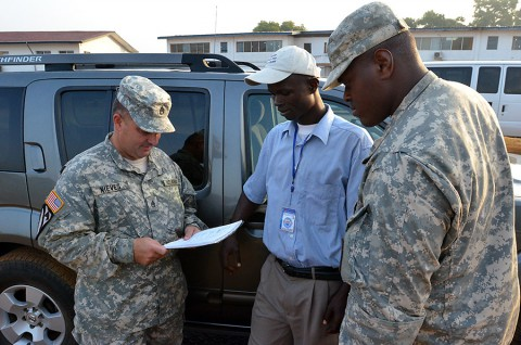 From left, Staff Sgt. Jose Nieves, a Bayamon, Puerto Rico, native and movement noncommissioned officer for Headquarters and Headquarters Company, 36th Engineer Brigade, talks to Haji A. Sheriff, a Liberia, Monrovia native and a driver, about his routes before he goes out on a mission to Buchanan, Liberia, Dec. 27, 2014, from the National Police Training Academy, Paynesville, Liberia, during Operation United Assistance. (Sgt. Ange Desinor, 13th Public Affairs Detachment)